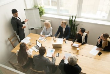 African american ceo boss in suit giving presentation at corporate team meeting concept, diverse executive group listening to black speaker explaining new plan coaching employees in conference room
