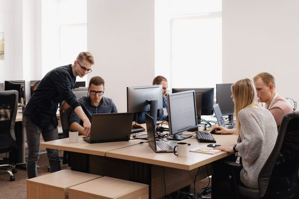 Full concentration at work. Group of young business people working and communicating while sitting at the office desk together with colleagues sitting in the background