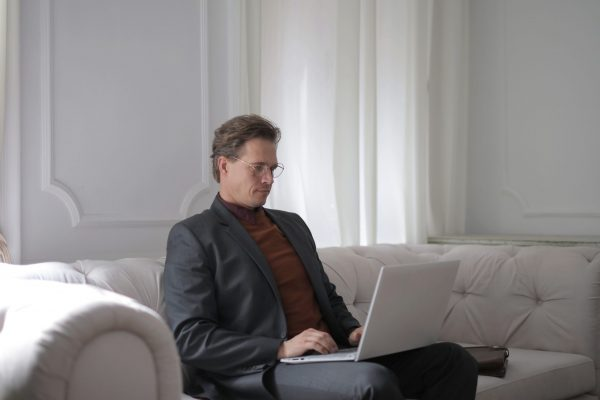 telework-a-man-sitting-on-a-white-couch-using-laptop-3760378